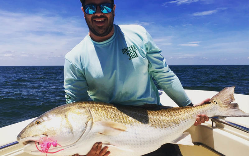 An image of an angler with a monster redfish aboard a Tidewater Charters fishing adventure.
