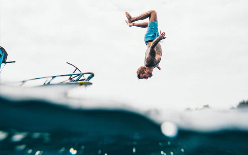 An image of a person doing a backflip off a boat into the waters of the Chesapeake Bay.